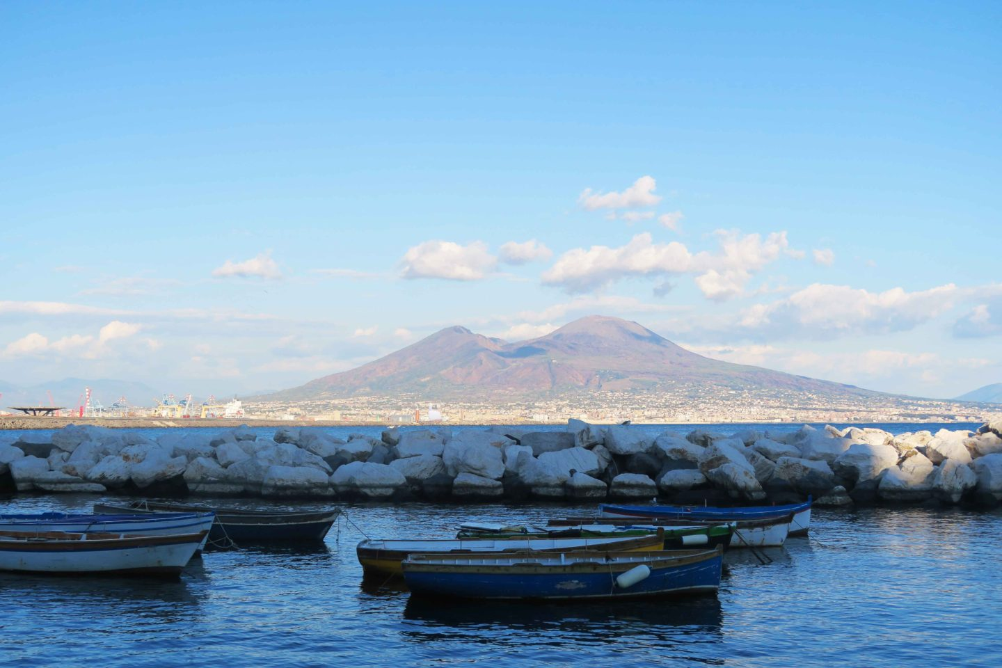 boats in the water at naples in front of mount vesuvius