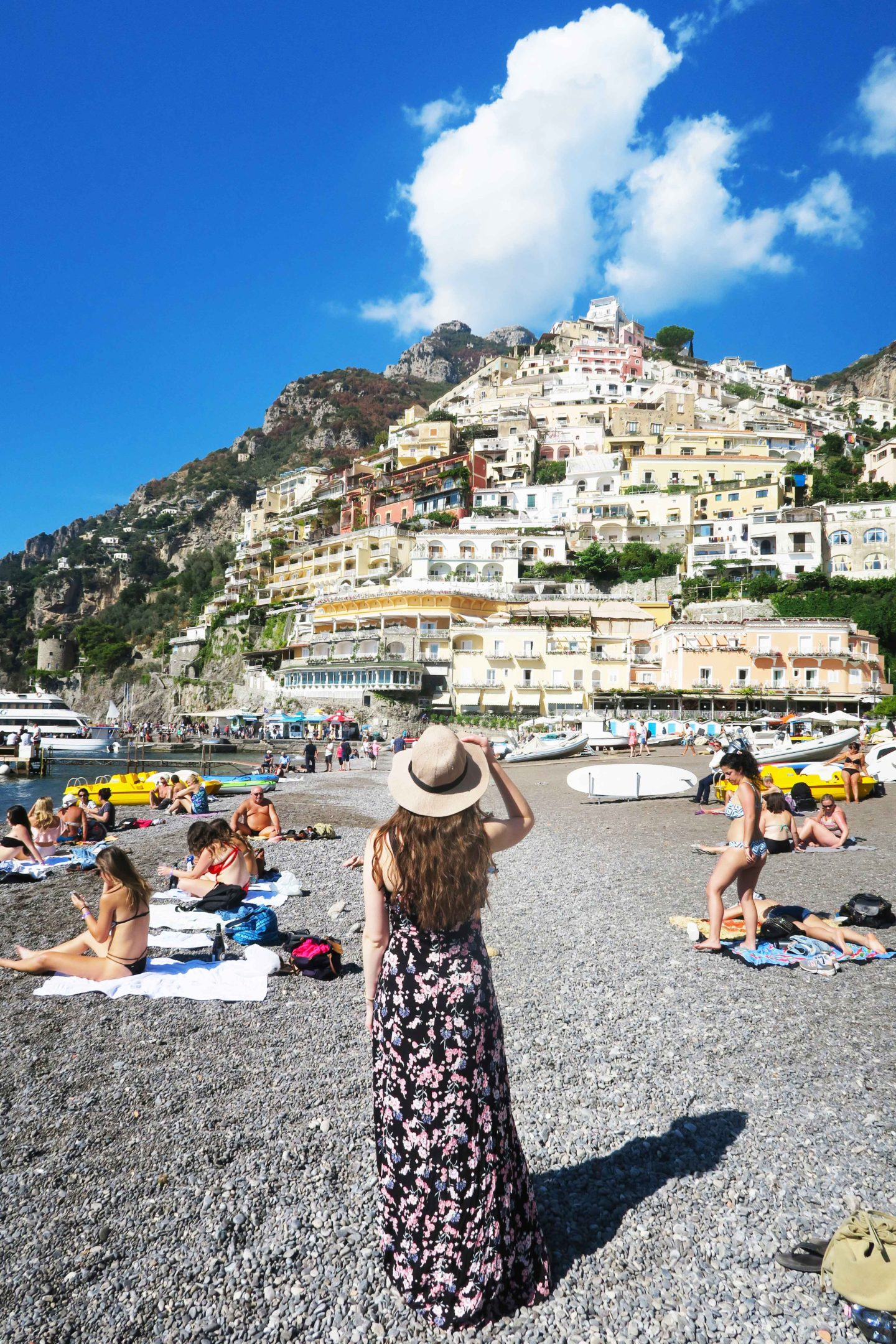 positano girl in sun dress and hat looking at the view