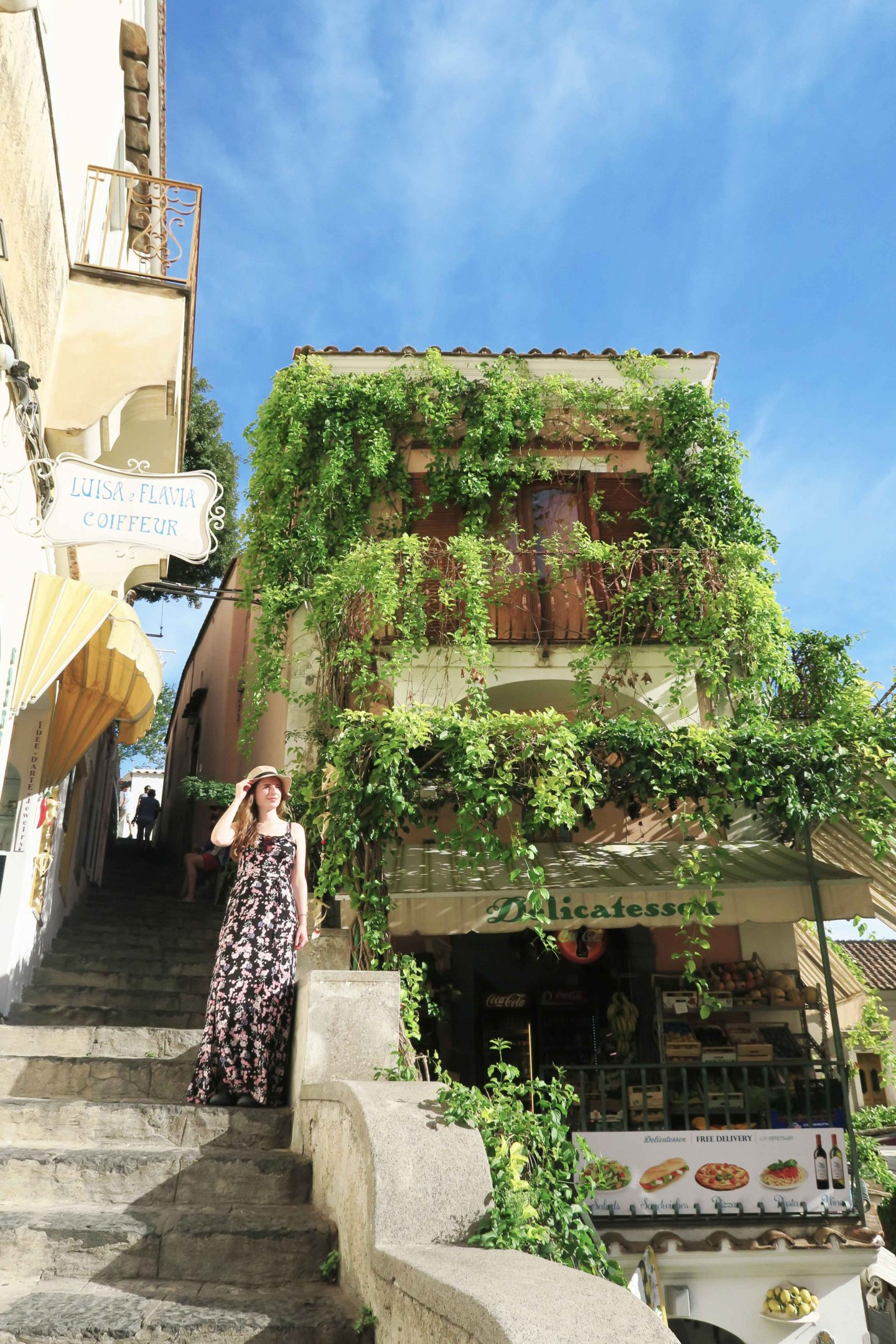 melissa carne standing on steps next to building in positano