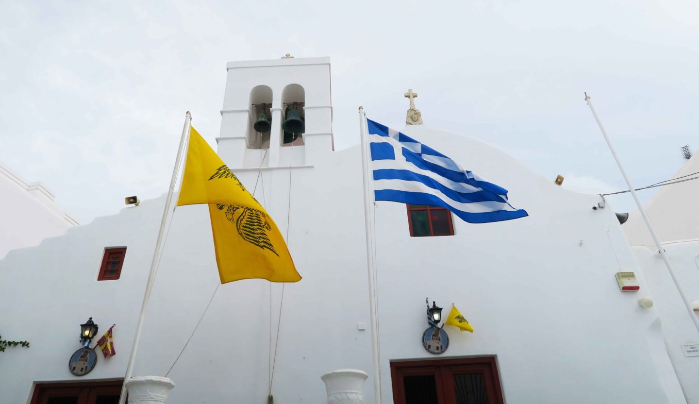 white church in mykonos town with greek flag