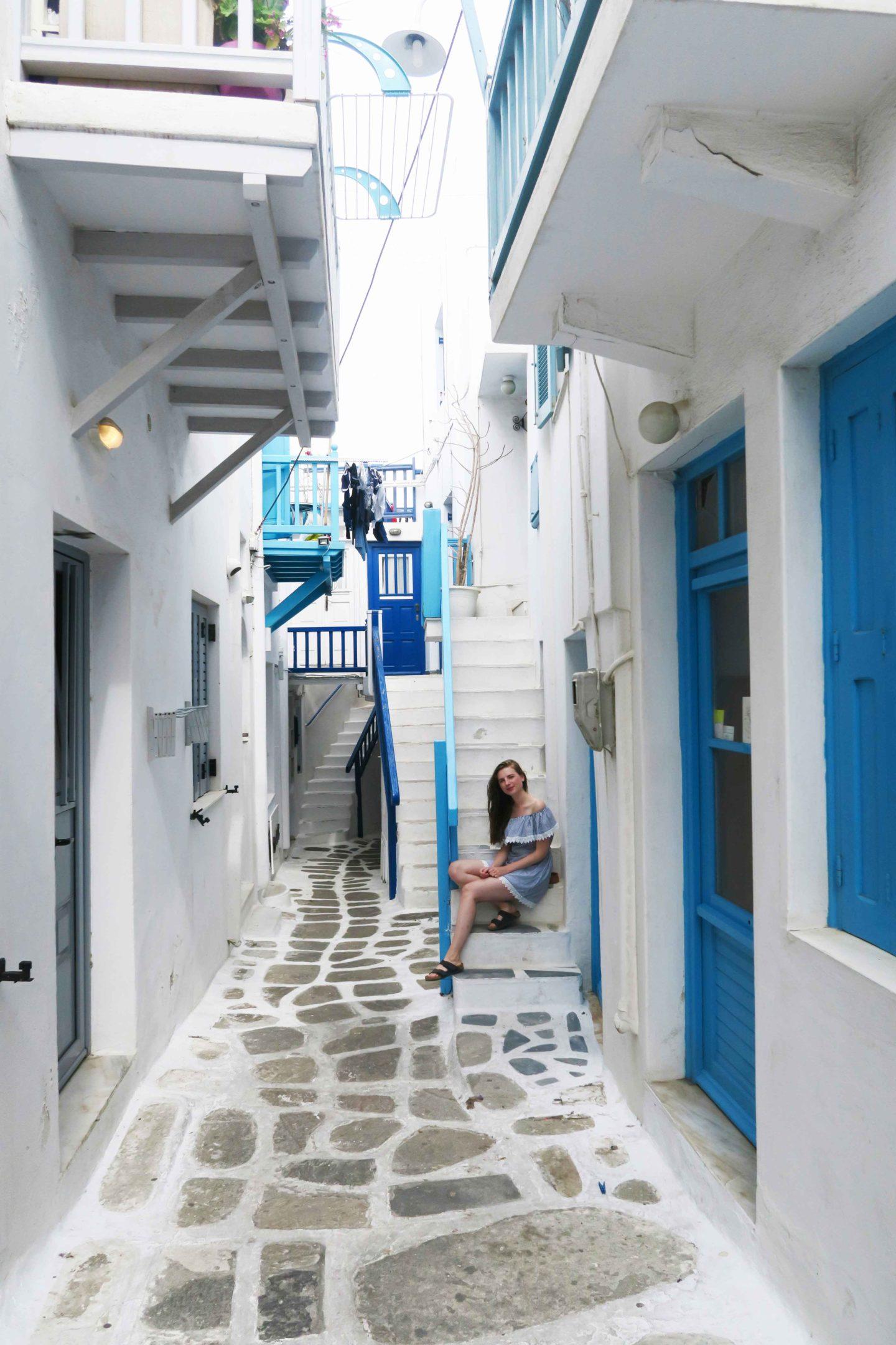 melissa carne sitting in white steps in mykonos town in greece