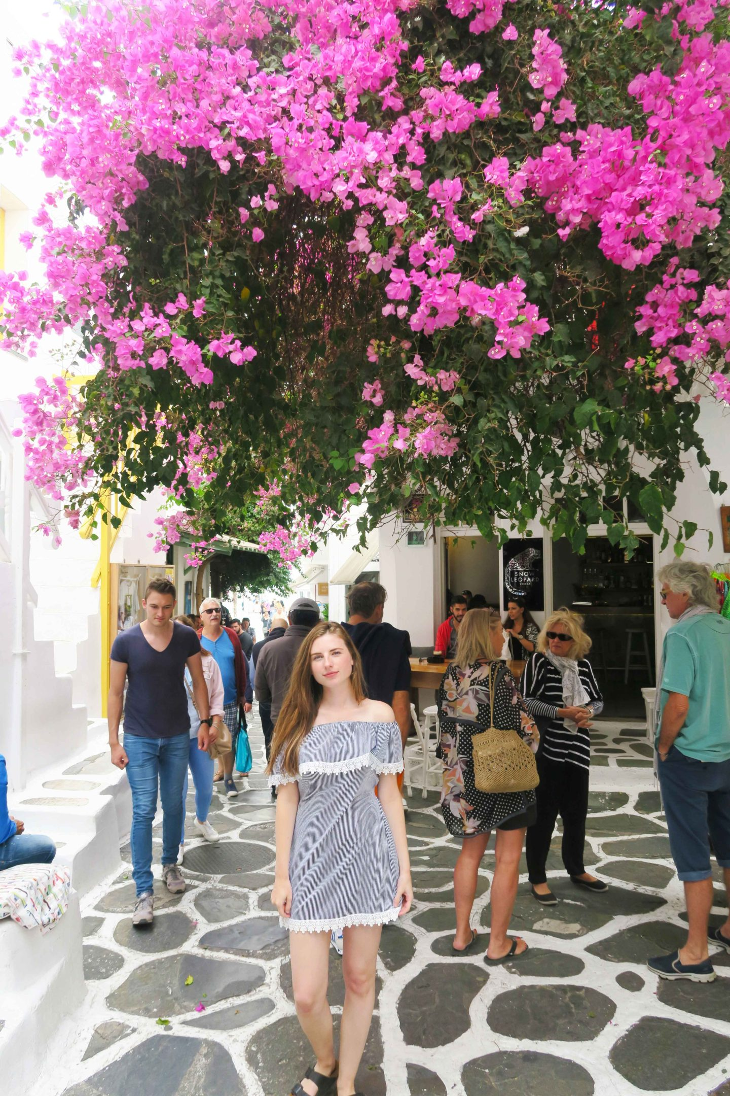 melissa carne standing under pink flowers in the centre of mykonos town