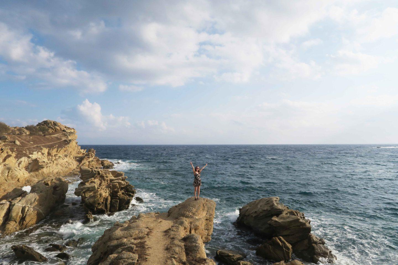 melissa carne standing on headland near platis gialos beach in mykonos