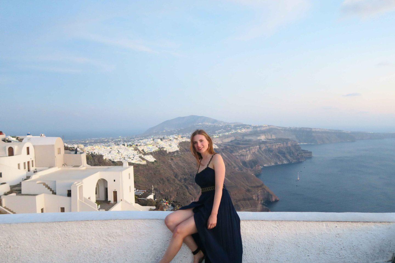melissa carne in greek dress sitting on white wall in santorini greece