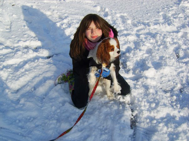 child in snow with dog