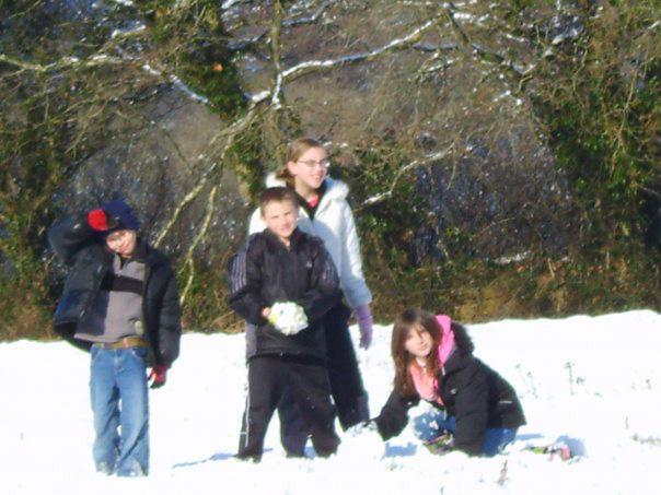 children building snowmen in field