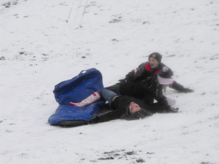 children falling of sled in snow
