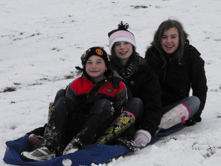 children on sled in snow