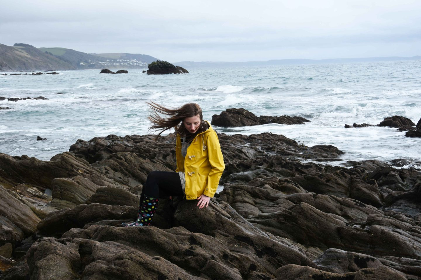 melissa carne in seasalt yellow coat sitting on rocks with windy hair in cornwall