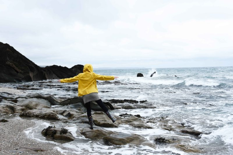 melissa carne balancing on rock in yellow coat by the sea in cornwall