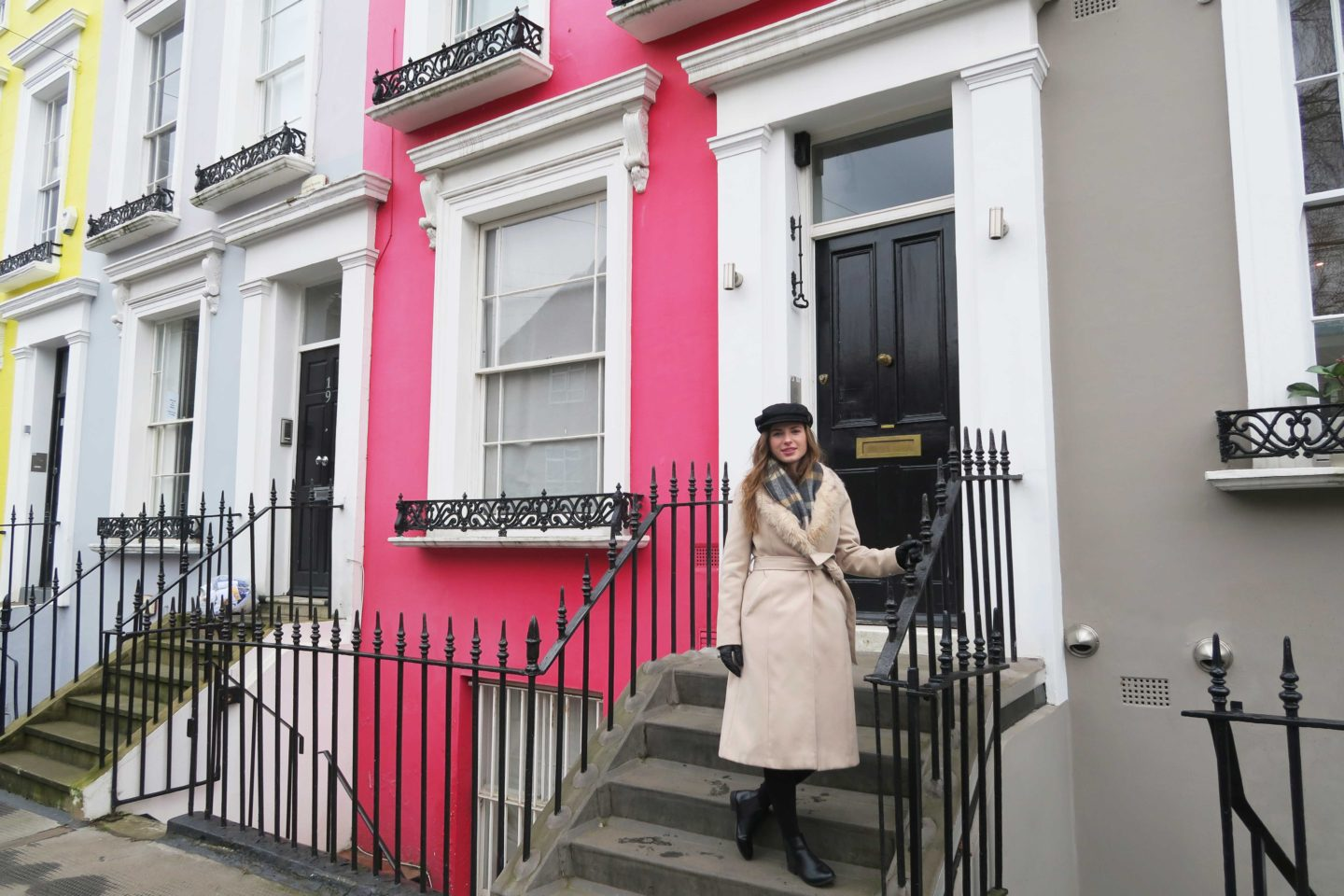 melissa carne standing in front of colourful houses in notting hill in london wearing a baker boy hat