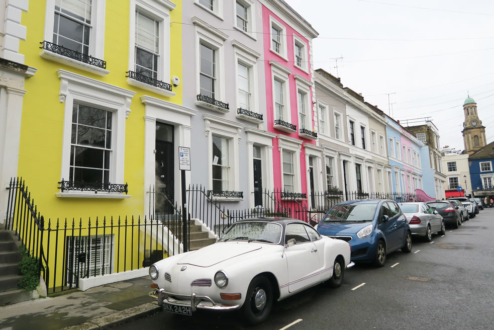 notting hill white vintage car parked outside of yellow terrace house