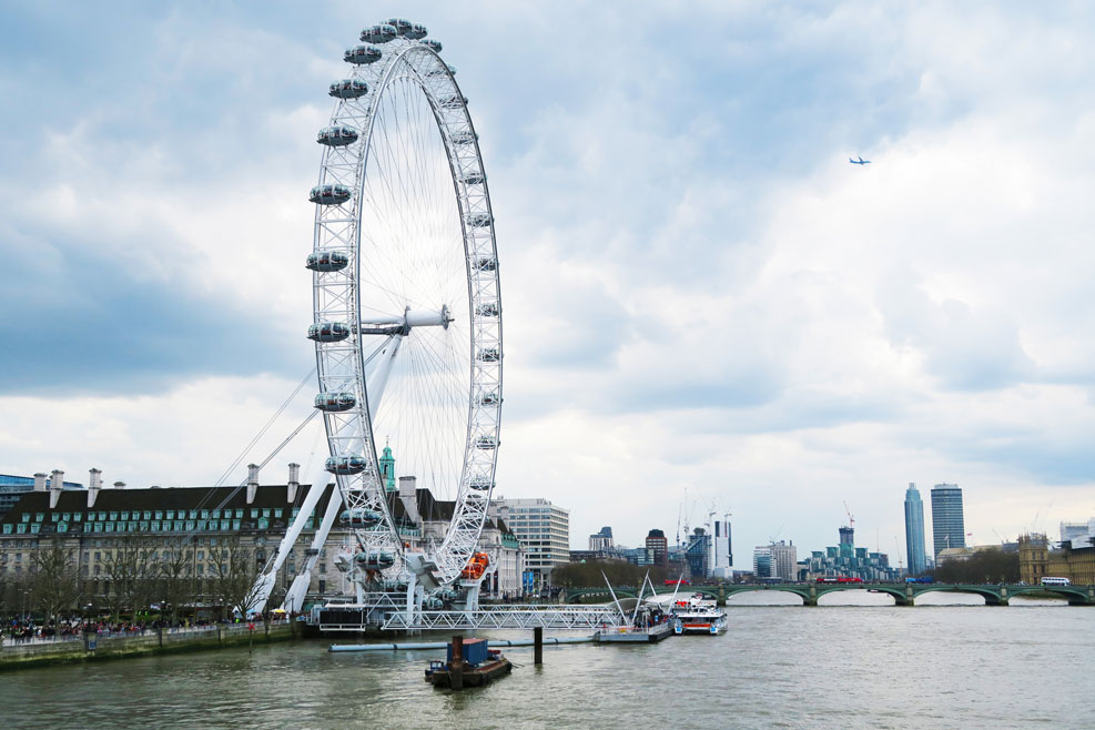 london eye with plane flying over top