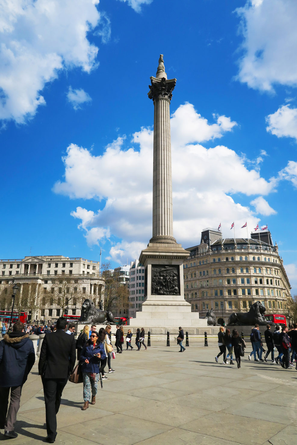 trafalgar square in london with blue sky and clouds