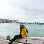 melissa carne sitting on wall at st ives harbour in cornwall