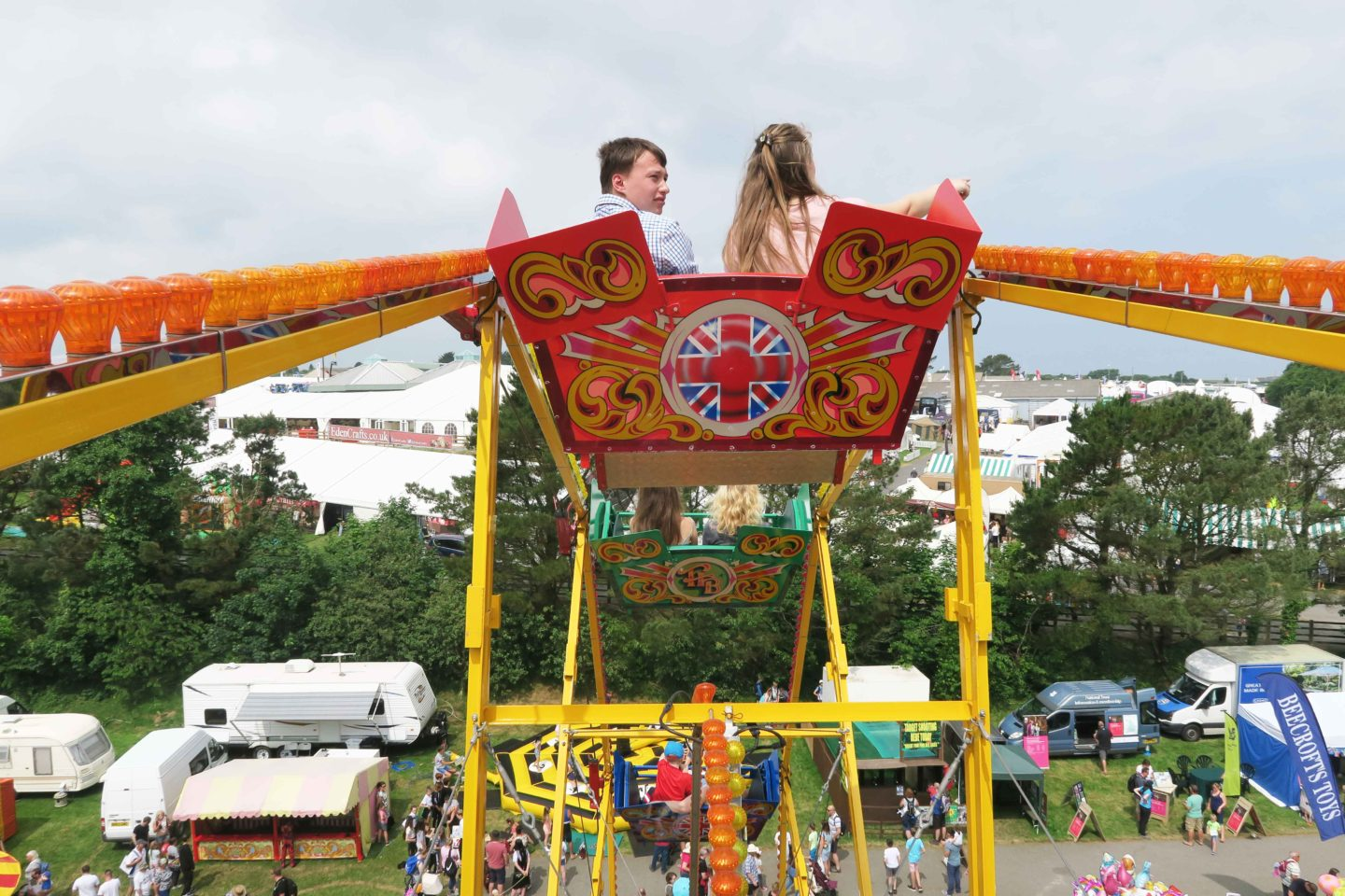 children on vintage ferris wheel at the fun fair in cornwall