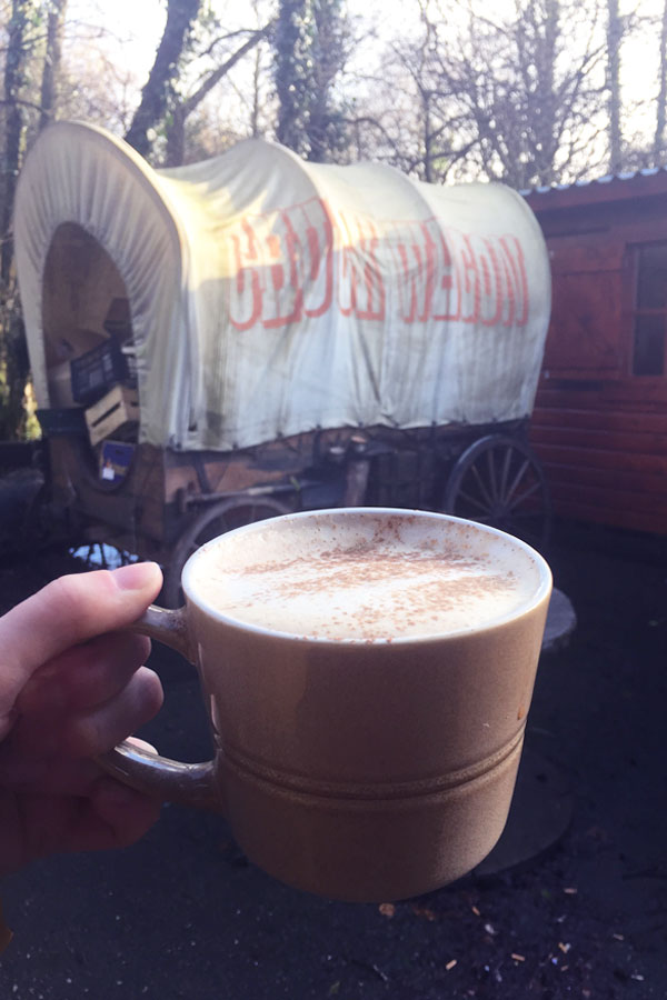 mug of chai latter in front of old band wagon