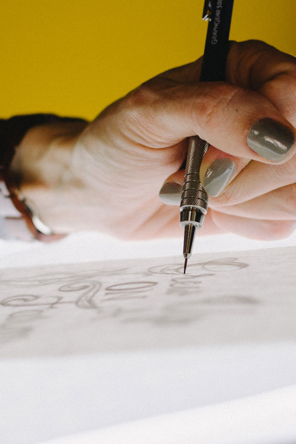 graphic designer drawing typography on a light box