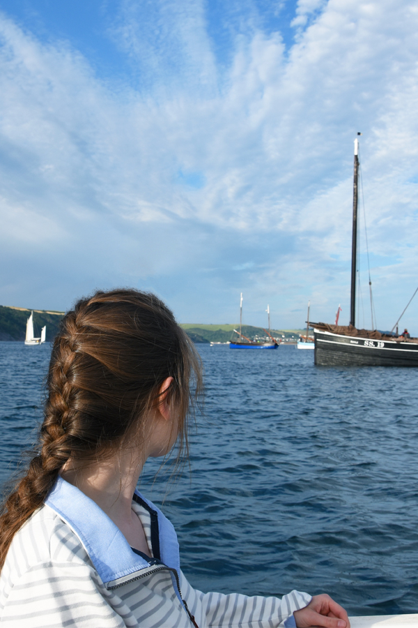 melissa carne wearing a french plait looking at lugger ships in looe in cornwall