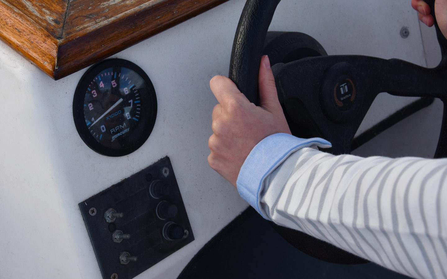 hand on a boat steering wheel