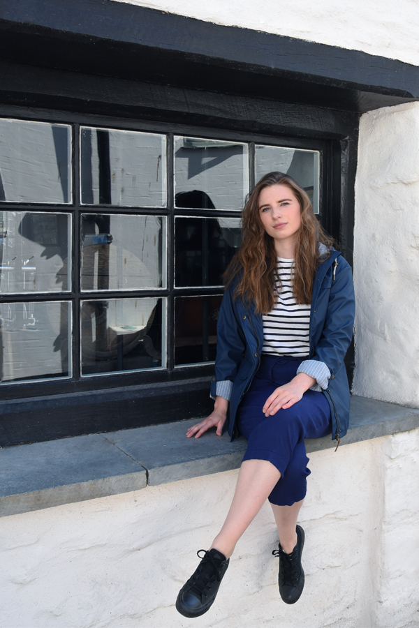 melissa carne sat on an old window sill in looe in cornwall wearing lighthouse clothing