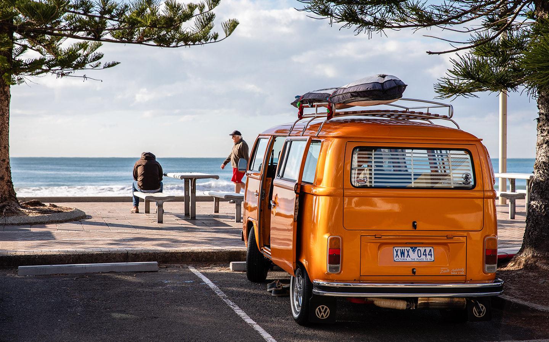 orange camper van parked by beach