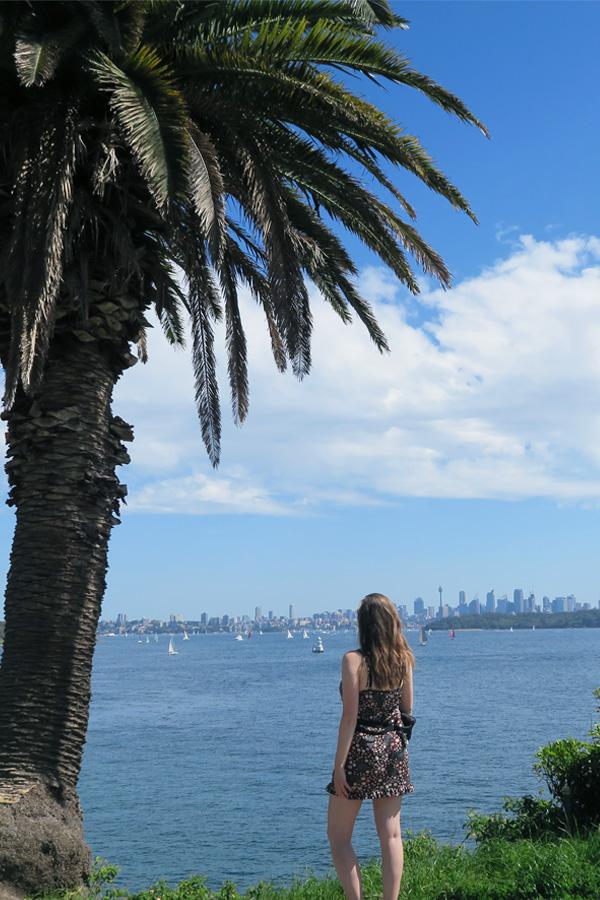 melissa carne standing next t palm tree overlooking sydney harbour in australia