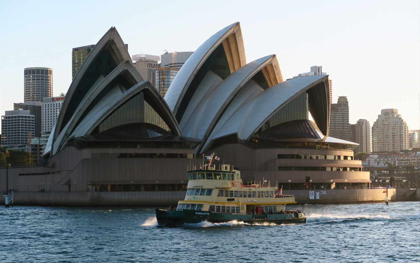 sydney opera house with ferry in front of it