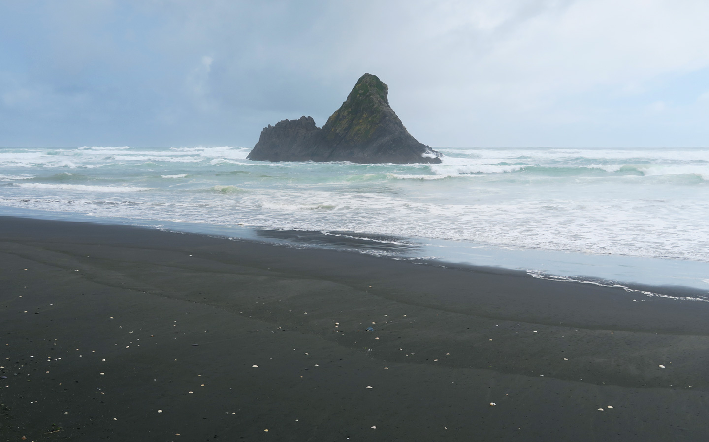 rock in sea in piha on black sand beach, new zealand