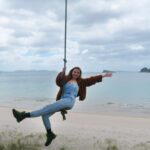 melissa carne on rope swing on hahei beach in new zealand