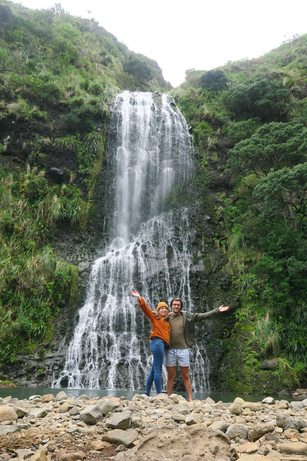 people in front of kare kare waterfall near piha in new zealand