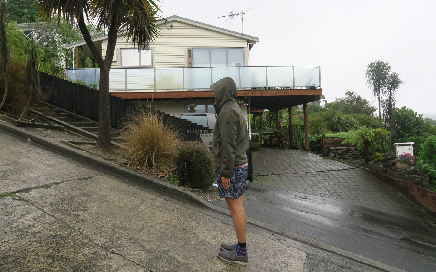 man standing on world's steepest street in dunedin in new zealand