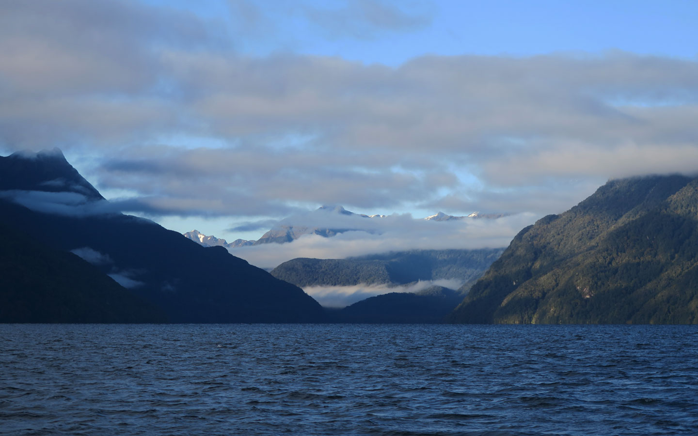 doubtful sound with clouds over hanging the mountains in new zealand