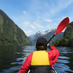 girl kayaking in doubtful sound in new zealand