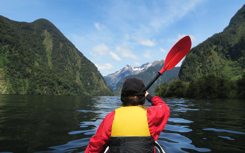 girl kayaking in doubtful sound in new zealand