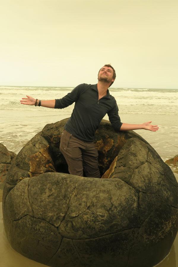 man hatching from moeraki boulder in new zealand