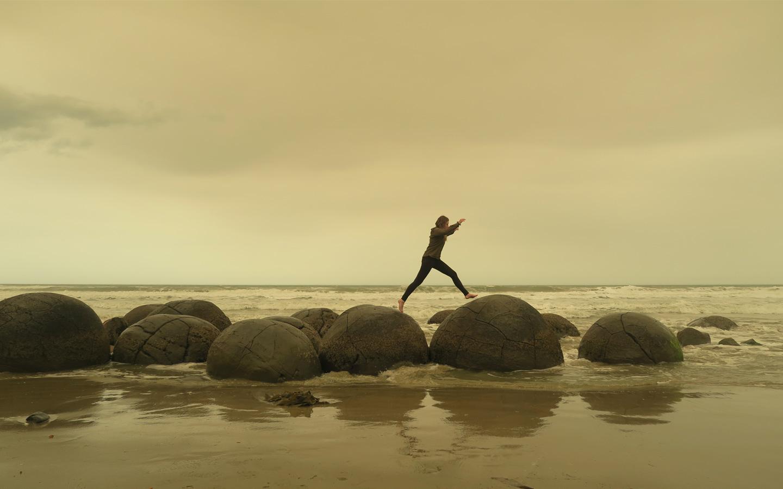 girl jumping on moeraki boulders in new zealand