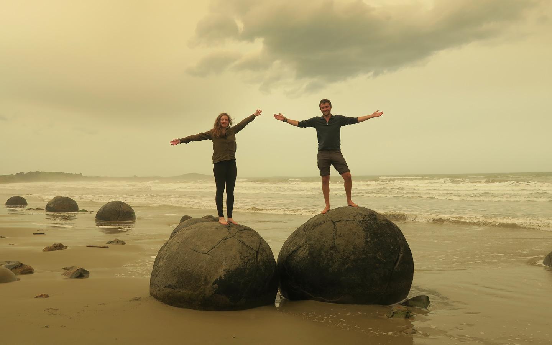 couple posing on moeraki boulders in new zealand