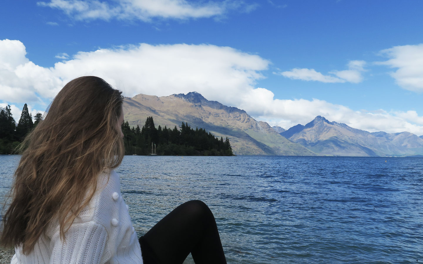 meliss carne sitting in front of mountains and lake wakatipu in new zealand