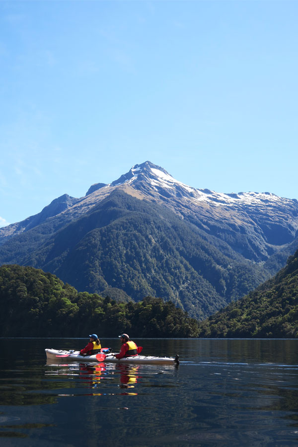 couple kayaking in a double kayak in doubtful sound with snow topped mountains
