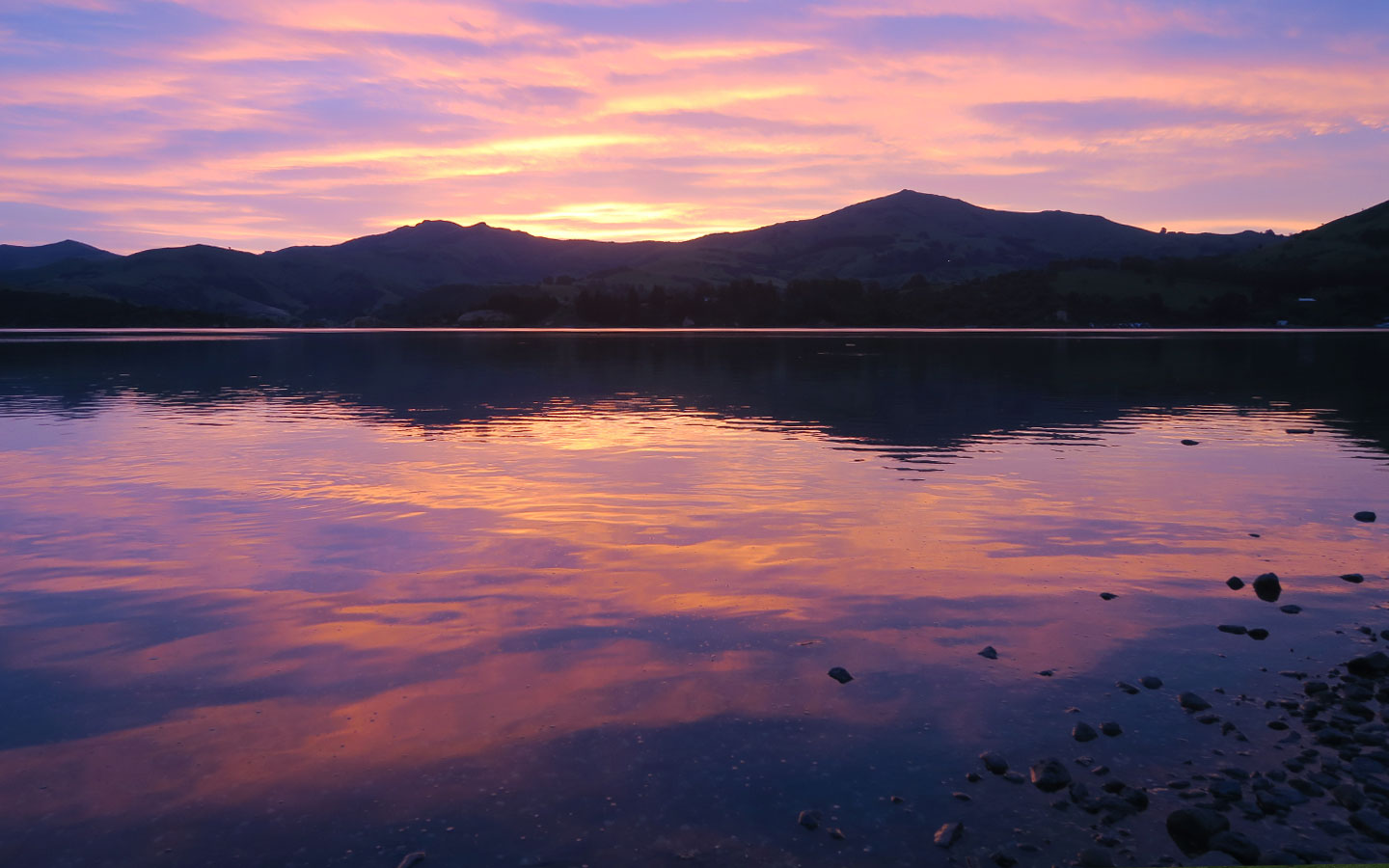 sunset with reflection of mountains in duvauchelle in new zealand