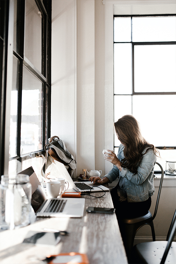 woman working at a desk with a macbook and external hard drive