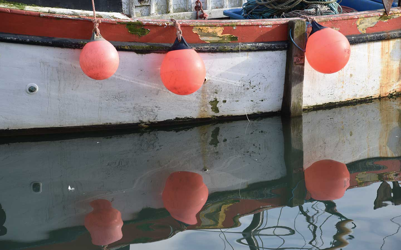 orange buoys on white fishing boat in cornwall