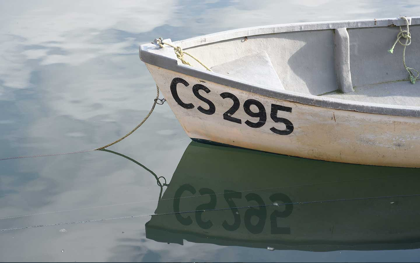 boat with numbers reflecting in the water at mevagissey