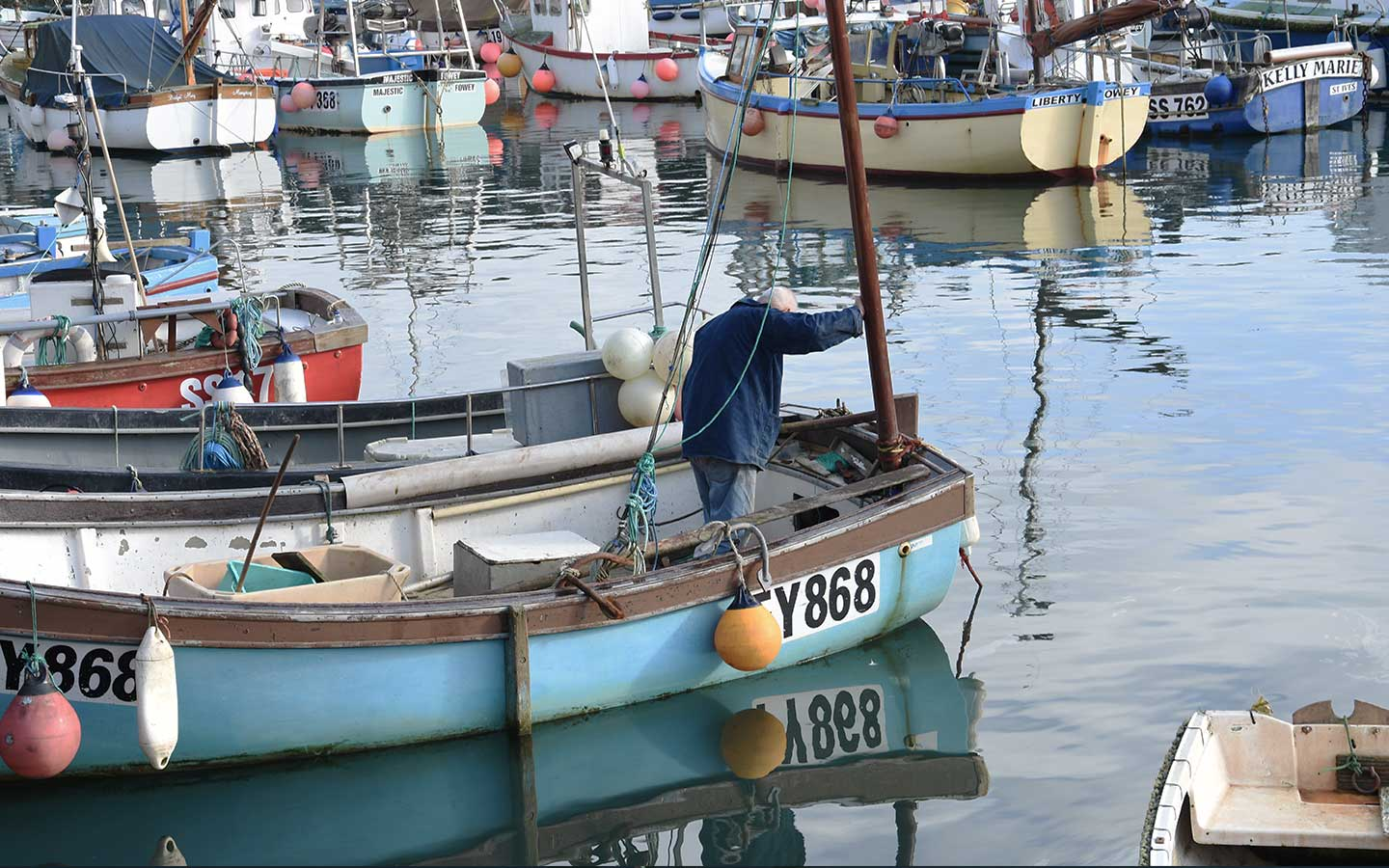 fisherman on boat on mevagissey harbour