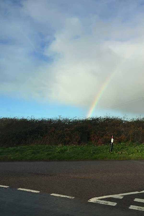 rainbow over cornish countryside road in cornwall