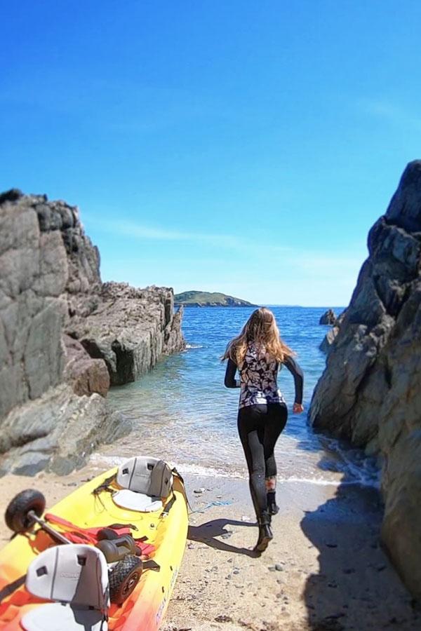 melissa carne running into sea next to sea kayak
