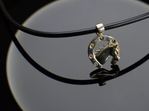 "925 Sterling Silver Horse Pendant With Black Leather Tube Model SYC 1CH040. This is ideal  for both males and females. Unique piece comes on contemporay style perfect for all outfits. Suitable for daily use,office use and perfect gift for our loved ones.  Importance of 925 Sterling Silver : We are aware of the trending style and beauty of Sterling silver but the Most Important Part of Sterling Silver 925 is the health benefits. Silver ions in Silver material has a proven record of antibiotic nature. The excellent way to obtain health improvement from 925 Sterling silver is when it get in touch with the skin. Silver is antibacterial too and helps to improve blood circulation and help remove toxins present in the human body. Some studies even mention about the defensive power of Silver Jewelry against Hazardous electro magnetic radiations emitting from Mobile phones or Laptops. Electrical and Thermal conductivity of Sterling silver 925 is the highlighted quality which indicate the capacity of Sterling silver to distribute electrical power as well as heat across the body.This is why Sterling silver boost the blood circulation, typical healing property and maintain the heat balance. If illnesses arrives , temperature level increases or hormonal change occurs Sterling silver wearing get appear more darker in color. Original 925 Sterling silver are more than 99% non allergic and skin friendly in nature. But Cheap Silver Plated Jewelry available in popular online sites ( in some websites they even wrongly mentioned it as sterling silver ) are dangerous for Skin especially those who have sensitive skin. We recommend to use Genuine quality Sterling Silver to avail health benefits and to avoid cheap fancy Silver Products.  Pure Silver and 92.5 Sterling Silver : 100% Pure Silver also known as Fine Silver is heavily soft in nature , very malleable and most likely it will get damaged within a short time. It's not Practically Possible to make Jewelry Products in 100 Percentage Pure silver due because Jewels will bend and have to be straightened. To tackle this and same time to remain the highest Silver Material Quality, 925 Sterling Silver is introduced. Sterling Silver contains 92.5 % Pure silver and alloys on other 7.5 % usually Copper. This helps sterling silver to increase hardness, durability, strength and reduce tarnishing. Silver designers can made Outstanding Trending Silverware collection with sterling silver 925 due to the mentioned properties. 925 Sterling silver Jewellery gives more beauty and elegant look. Sterling silver even suits for black skin tones. Sterling silver enhances beauty and give a pretty modern look. ""Sterling silver 925"" word is associated with superior quality since ancient times. Silverycraft Luxury Sterling silver Jewel's are affordable too.  Caring the Valuable Silver Jewels : Silverycraft Products especially Sterling Silver 925 need less care compared to other brands. Still it's important to do proper care mainly Keep your precious Silver away from high humidity, Chemicals, Oils, Perfumes, Hair products, water containing Chlorine etc which may cause tarnish in silver. Precious Stones used in Silver Jewels need Special care. Flannel Treated Bags & cloth helps to retard tarnishing in Silver while Long Storage or you can use a Cloth pouch or Separate box for Storage at Home. You can Clean Sterling silver using very soft Banyan cloth. After the tarnish disappears ,rinse your Silver jewellery with water and dry it using a soft cloth. Its is easy to care and usually no maintenance issue occurs. Usual Tarnishing or Silver Color Variation (oxidation) due to interaction with atmosphere is common and it also indicate the symbol of Original silver content in the jewellery. Regular Caring will definitely reduce tarnishing to a great extend.SILVERYCRAFT original Silver craft jewellery in India and genuine sterling silver 92.5 jewelry collection silver products silver gifts silver wedding collections female male kids silver sterling 925 silver jewels rare collection silvers Fashion silver fashonable silver crafts Indian made silver e commerce website online silver purchase buy silver jewelleries online SILVERYCRAFT Silver jewellery's Silvery crafts crafted silvers India's fine quality silver at www.silverycraft.com"
