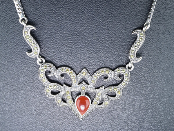 "925 Sterling Oxidised Silver chain Crown Necklace With Marcasite Stone And Red Carnelian Stone Model SYC 1N039. This is ideal  for womens and girls. Unique piece comes on contemporary style perfect for all outfits.  Suitable for birthday functions, wedding ceremony, valentine gifts,engagements and perfect gift for our loved ones. This stylish necklace makes you feel more beautiful and elegant look. Importance of 925 Sterling Silver : We are aware of the trending style and beauty of Sterling silver but the Most Important Part of Sterling Silver 925 is the health benefits. Silver ions in Silver material has a proven record of antibiotic nature. The excellent way to obtain health improvement from 925 Sterling silver is when it get in touch with the skin. Silver is antibacterial too and helps to improve blood circulation and help remove toxins present in the human body. Some studies even mention about the defensive power of Silver Jewelry against Hazardous electro magnetic radiations emitting from Mobile phones or Laptops. Electrical and Thermal conductivity of Sterling silver 925 is the highlighted quality which indicate the capacity of Sterling silver to distribute electrical power as well as heat across the body.This is why Sterling silver boost the blood circulation, typical healing property and maintain the heat balance. If illnesses arrives , temperature level increases or hormonal change occurs Sterling silver wearing get appear more darker in color. Original 925 Sterling silver are more than 99% non allergic and skin friendly in nature. But Cheap Silver Plated Jewelry available in popular online sites ( in some websites they even wrongly mentioned it as sterling silver ) are dangerous for Skin especially those who have sensitive skin. We recommend to use Genuine quality Sterling Silver to avail health benefits and to avoid cheap fancy Silver Products.  Pure Silver and 92.5 Sterling Silver : 100% Pure Silver also known as Fine Silver is heavily soft in nature , very malleable and most likely it will get damaged within a short time. It's not Practically Possible to make Jewelry Products in 100 Percentage Pure silver due because Jewels will bend and have to be straightened. To tackle this and same time to remain the highest Silver Material Quality, 925 Sterling Silver is introduced. Sterling Silver contains 92.5 % Pure silver and alloys on other 7.5 % usually Copper. This helps sterling silver to increase hardness, durability, strength and reduce tarnishing. Silver designers can made Outstanding Trending Silverware collection with sterling silver 925 due to the mentioned properties. 925 Sterling silver Jewellery gives more beauty and elegant look. Sterling silver even suits for black skin tones. Sterling silver enhances beauty and give a pretty modern look. ""Sterling silver 925"" word is associated with superior quality since ancient times. Silverycraft Luxury Sterling silver Jewel's are affordable too.  Caring the Valuable Silver Jewels : Silverycraft Products especially Sterling Silver 925 need less care compared to other brands. Still it's important to do proper care mainly Keep your precious Silver away from high humidity, Chemicals, Oils, Perfumes, Hair products, water containing Chlorine etc which may cause tarnish in silver. Precious Stones used in Silver Jewels need Special care. Flannel Treated Bags & cloth helps to retard tarnishing in Silver while Long Storage or you can use a Cloth pouch or Separate box for Storage at Home. You can Clean Sterling silver using very soft Banyan cloth. After the tarnish disappears ,rinse your Silver jewellery with water and dry it using a soft cloth. Its is easy to care and usually no maintenance issue occurs. Usual Tarnishing or Silver Color Variation (oxidation) due to interaction with atmosphere is common and it also indicate the symbol of Original silver content in the jewellery. Regular Caring will definitely reduce tarnishing to a great extend.SILVERYCRAFT original Silver craft jewellery in India and genuine sterling silver 92.5 jewelry collection silver products silver gifts silver wedding collections female male kids silver sterling 925 silver jewels rare collection silvers Fashion silver fashonable silver crafts Indian made silver e commerce website online silver purchase buy silver jewelleries online SILVERYCRAFT Silver jewellery's Silvery crafts crafted silvers India's fine quality silver at www.silverycraft.com"