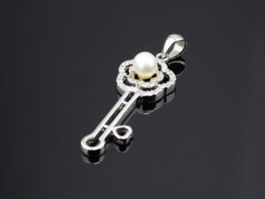 "925 Sterling Silver Locket Key Shape  with white stones and pearl pendant Model SYC 2L67. This is ideal for women and girls. Unique piece comes on contemporary style perfect for all outfits. Suitable for birthday functions, wedding ceremony, valentine gifts,engagements and perfect gift for our loved ones. Importance of 925 Sterling Silver : We are aware of the trending style and beauty of Sterling silver but the Most Important Part of Sterling Silver 925 is the health benefits. Silver ions in Silver material has a proven record of antibiotic nature. The excellent way to obtain health improvement from 925 Sterling silver is when it get in touch with the skin. Silver is antibacterial too and helps to improve blood circulation and help remove toxins present in the human body. Some studies even mention about the defensive power of Silver Jewelry against Hazardous electro magnetic radiations emitting from Mobile phones or Laptops. Electrical and Thermal conductivity of Sterling silver 925 is the highlighted quality which indicate the capacity of Sterling silver to distribute electrical power as well as heat across the body.This is why Sterling silver boost the blood circulation, typical healing property and maintain the heat balance. If illnesses arrives , temperature level increases or hormonal change occurs Sterling silver wearing get appear more darker in color. Original 925 Sterling silver are more than 99% non allergic and skin friendly in nature. But Cheap Silver Plated Jewelry available in popular online sites ( in some websites they even wrongly mentioned it as sterling silver ) are dangerous for Skin especially those who have sensitive skin. We recommend to use Genuine quality Sterling Silver to avail health benefits and to avoid cheap fancy Silver Products.  Pure Silver and 92.5 Sterling Silver : 100% Pure Silver also known as Fine Silver is heavily soft in nature , very malleable and most likely it will get damaged within a short time. It's not Practically Possible to make Jewelry Products in 100 Percentage Pure silver due because Jewels will bend and have to be straightened. To tackle this and same time to remain the highest Silver Material Quality, 925 Sterling Silver is introduced. Sterling Silver contains 92.5 % Pure silver and alloys on other 7.5 % usually Copper. This helps sterling silver to increase hardness, durability, strength and reduce tarnishing. Silver designers can made Outstanding Trending Silverware collection with sterling silver 925 due to the mentioned properties. 925 Sterling silver Jewellery gives more beauty and elegant look. Sterling silver even suits for black skin tones. Sterling silver enhances beauty and give a pretty modern look. ""Sterling silver 925"" word is associated with superior quality since ancient times. Silverycraft Luxury Sterling silver Jewel's are affordable too.  Caring the Valuable Silver Jewels : Silverycraft Products especially Sterling Silver 925 need less care compared to other brands. Still it's important to do proper care mainly Keep your precious Silver away from high humidity, Chemicals, Oils, Perfumes, Hair products, water containing Chlorine etc which may cause tarnish in silver. Precious Stones used in Silver Jewels need Special care. Flannel Treated Bags & cloth helps to retard tarnishing in Silver while Long Storage or you can use a Cloth pouch or Separate box for Storage at Home. You can Clean Sterling silver using very soft Banyan cloth. After the tarnish disappears ,rinse your Silver jewellery with water and dry it using a soft cloth. Its is easy to care and usually no maintenance issue occurs. Usual Tarnishing or Silver Color Variation (oxidation) due to interaction with atmosphere is common and it also indicate the symbol of Original silver content in the jewellery. Regular Caring will definitely reduce tarnishing to a great extend.SILVERYCRAFT original Silver craft jewellery in India and genuine sterling silver 92.5 jewelry collection silver products silver gifts silver wedding collections female male kids silver sterling 925 silver jewels rare collection silvers Fashion silver fashonable silver crafts Indian made silver e commerce website online silver purchase buy silver jewelleries online SILVERYCRAFT Silver jewellery's Silvery crafts crafted silvers India's fine quality silver at www.silverycraft.com"